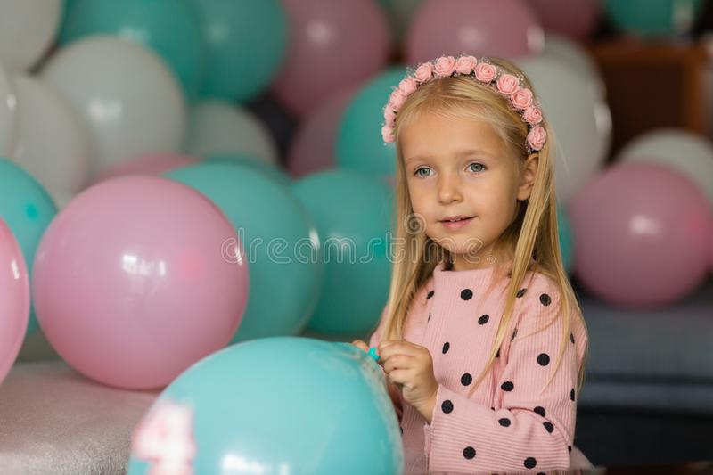 Indoor shot of pretty joyful little girl with blonde hair looking at cake, celebrate 4 years old birthday, wear stock images