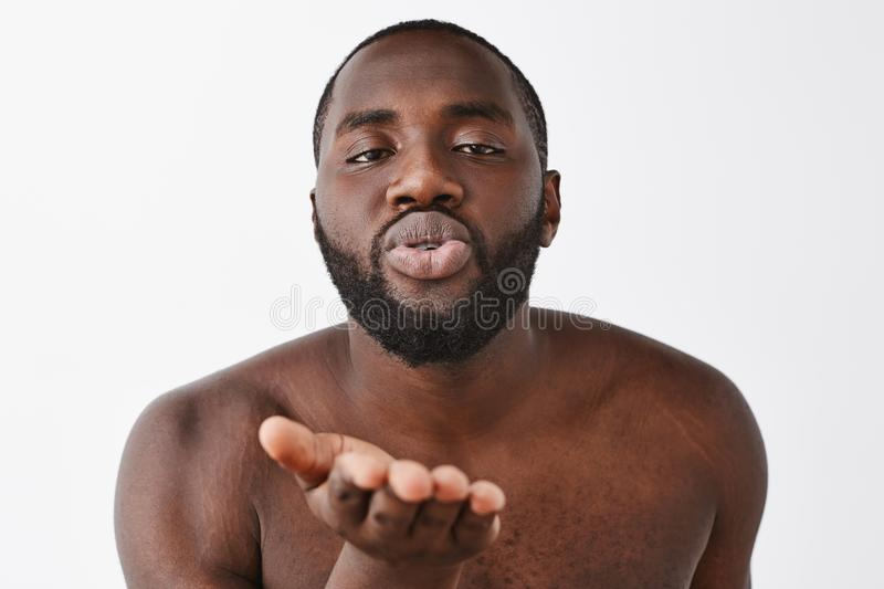 Indoor shot of relaxed flirty and sensual attractive dark-skinned male model with beard, posing naked over grey wall stock photography