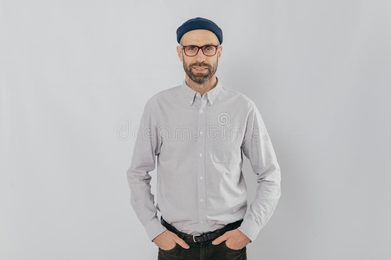 Indoor shot of satisfied Caucasian man in spectacles with bristle, keeps hands in pockets, dressed in formal stylish clothes, has royalty free stock photo