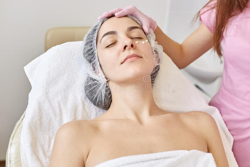 Indoor shot of satisfied relaxed woman closing her eyes while laying on coach, getting cosmetic service, having nourishing cream. Indoor shot of satisfied stock photos
