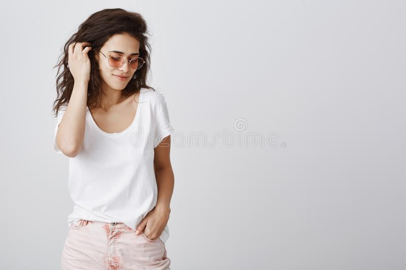 Indoor shot of sensual feminine woman touching curly hair with hand, posing and looking down with flirty smile, wearing. Trendy sunglasses and colorful stylish royalty free stock image