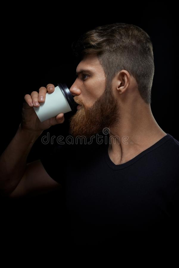 Brutal bearded man drinking coffee to go royalty free stock images