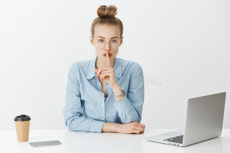 Indoor shot of serious good-looking blond woman in glasses sitting in office near laptop and smartphone, saying shh. While showing shush gesture, sharing secret stock photography