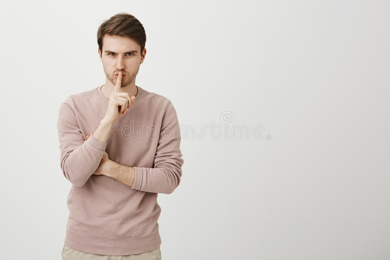 Indoor shot of serious good-looking caucasian man with bristle holding index finger over mouth saying shh, being focused. And confident, standing over gray stock photos