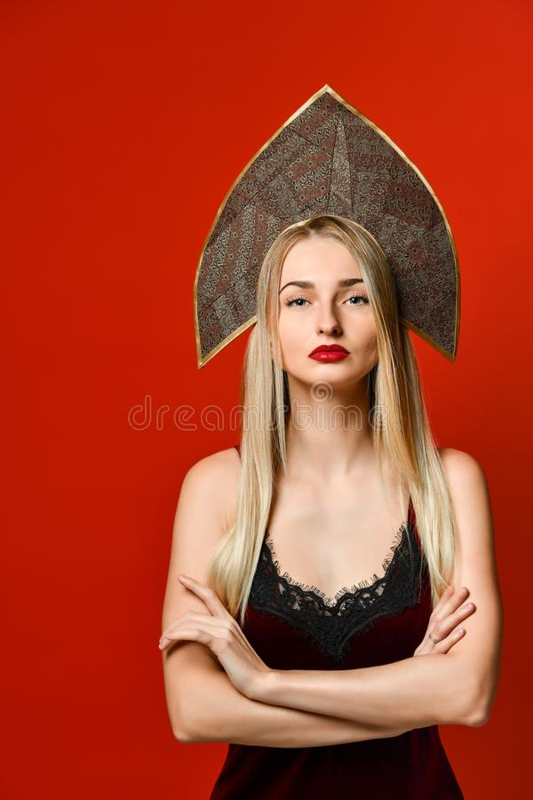 Indoor shot of serious strict young female dressed velvet dress keeping arms folded stock photo