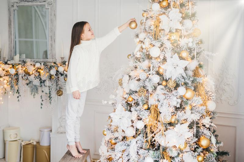 Indoor shot of small kid in white clothes, decorates New Year tree, stands on tiptoe, holds decoration in hands, does everything w. Ithout parent`s help. House stock image