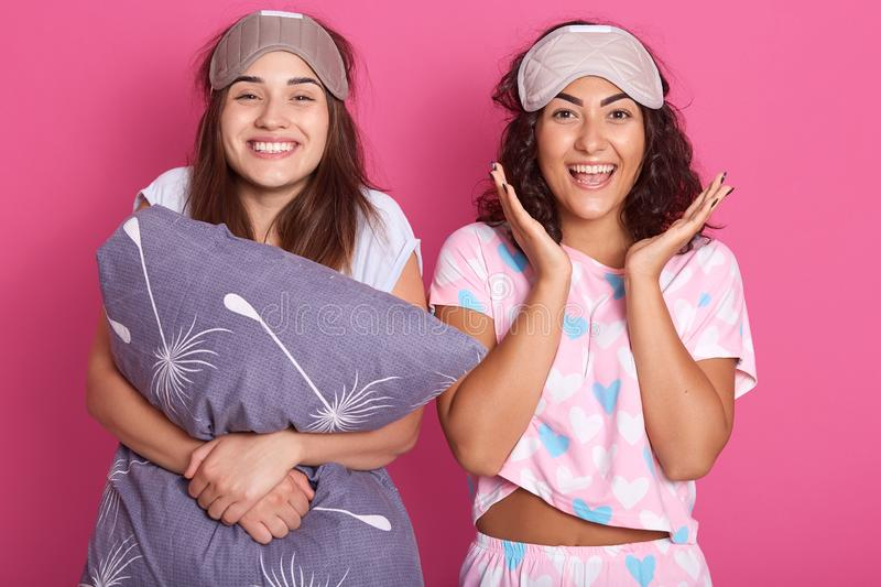 Indoor shot of smiling women with sleep masks on head, wearing pajamas standing isolated over pink studio background, having royalty free stock photo