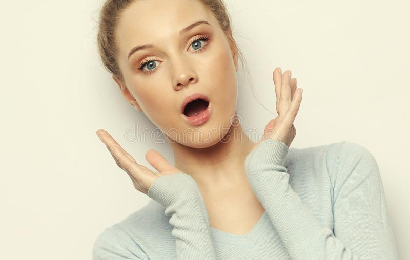 Indoor shot of stupefied shocked blonde woman keeps mouth widely opened, looks at camera royalty free stock photos