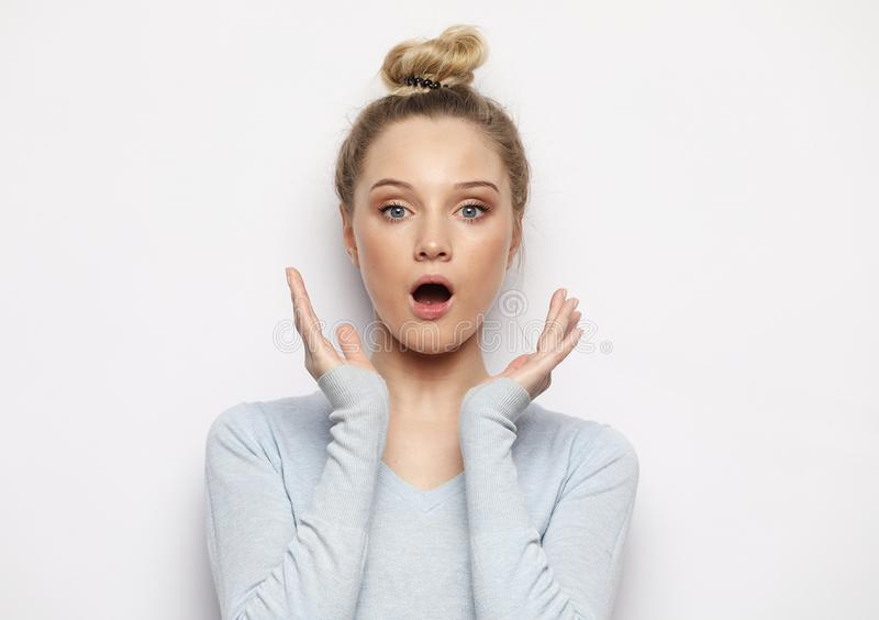 Indoor shot of stupefied shocked blonde woman keeps mouth widely opened, looks at camera, wears casual clothes stock photo