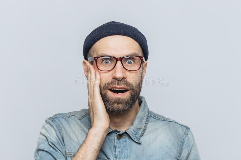 Indoor shot of surprised handsome man stares at camera, keeps hand on cheek, wears glasses and stylish clothing, isolated over whi royalty free stock images