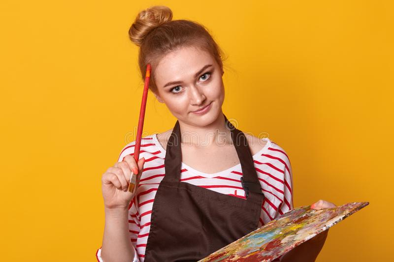 Indoor shot of thoughtful creative artist with paint equipment, touching head with brush, thinking over concept of masterpiece, royalty free stock photography