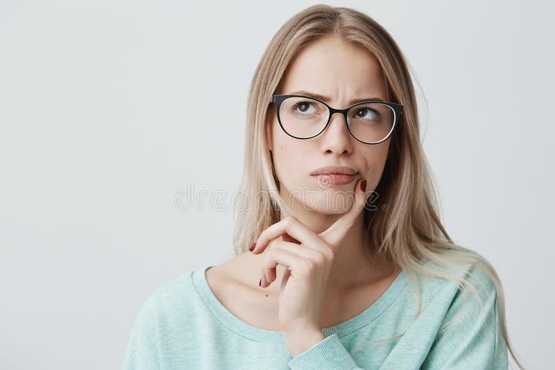 Indoor shot of thoughtful pretty woman has long blonde hair with stylish eyewear, looks aside with pensive expression stock photos