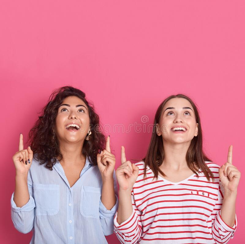 Indoor shot of two european women friends wearingcasual clothes posing isolated over pink background. People lifestyle concept. royalty free stock photo
