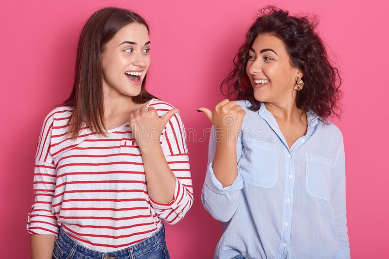 Indoor shot of two young beautiful girls pointing towards each other, brunette women dress shirts, standing against pink studio royalty free stock photos