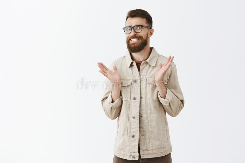 Indoor shot of unsure intense male office worker explaining tough trouble clenching teeth frowning looking worried and. Clueless shaking palms in unaware and royalty free stock photo