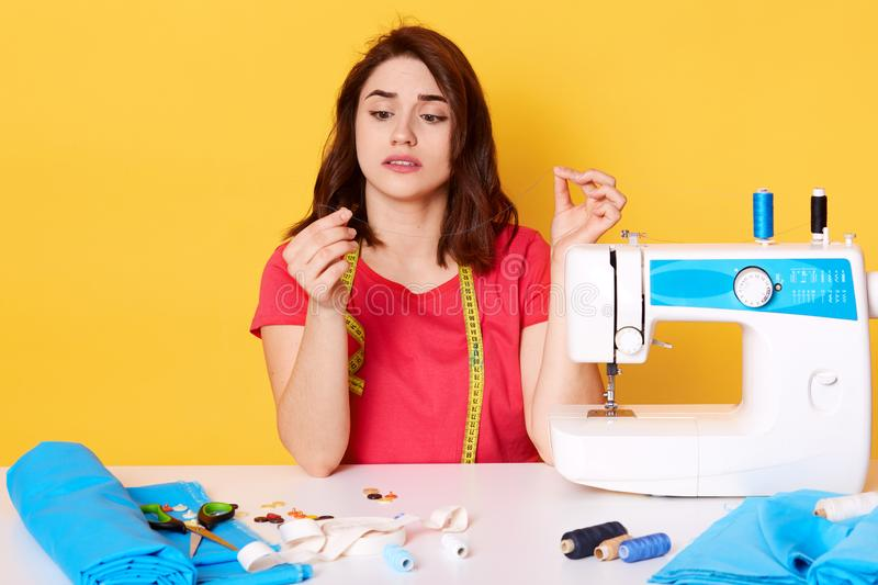 Indoor shot of upset busy young woman in red t shirt sitting at desk full of sewing tools and holding torn thread in workshop,. Model posing isolated on yellow stock photo