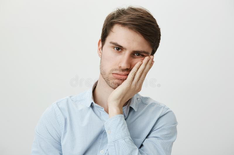 Indoor shot of upset irritated caucasian guy leaning on palm and sighing at camera, being bored and fed up of annoying stock photo