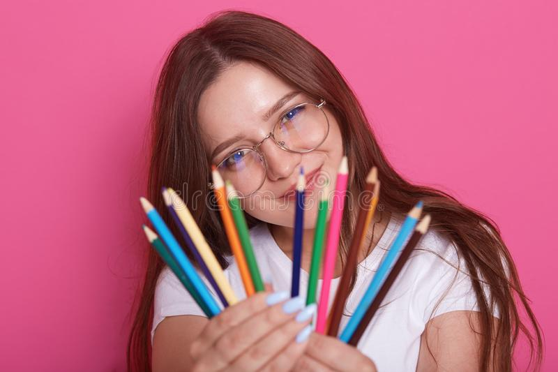 Indoor shot of young beautiful girl artist wearing white casual shirt and eyewear, model posing with colored pencils in her hands royalty free stock photos