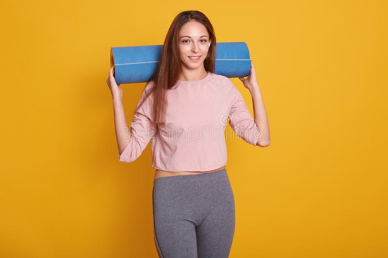 Indoor shot of young happy beautiful Caucasian woman,looks smiling at camera, holding yoga mat over her shoulder, ready for gym, royalty free stock photography