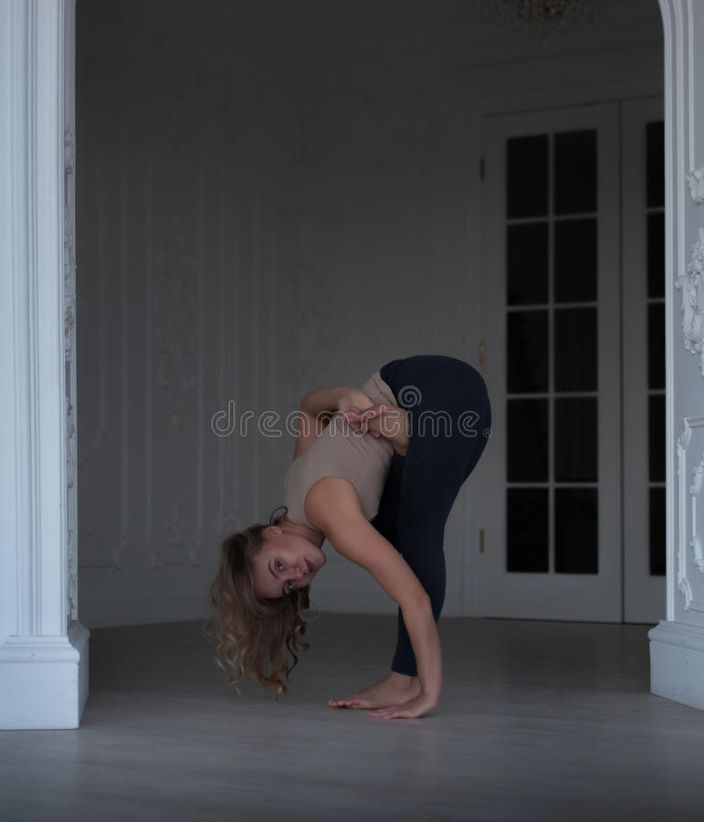 Indoor shot of a young woman doing yoga. In white interior royalty free stock image