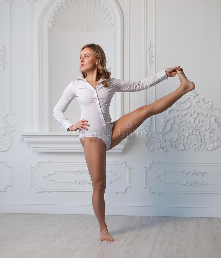 Indoor shot of a young woman doing yoga. Indoor shot of a young woman doing yoga in the white interior stock images