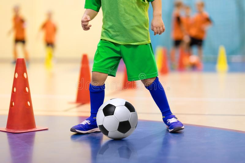 Indoor soccer young player with a soccer ball in a sports hall. Player in green uniform. Sport background. Football futsal training for children. Soccer royalty free stock photo