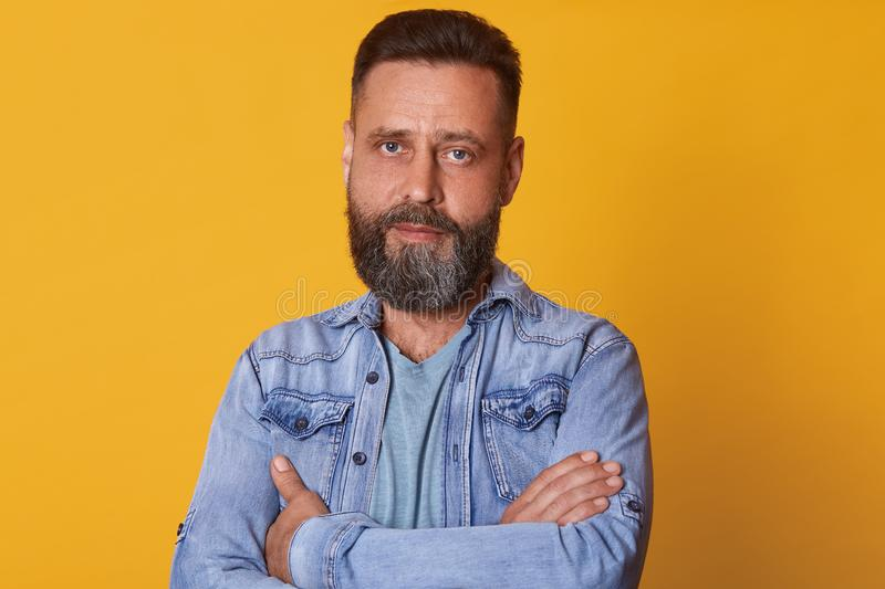 Indoor studio close up portrait of strong charismatic bearded blue eyed man standing with folded arms isolated over bright yellow. Background in studio, having stock photography