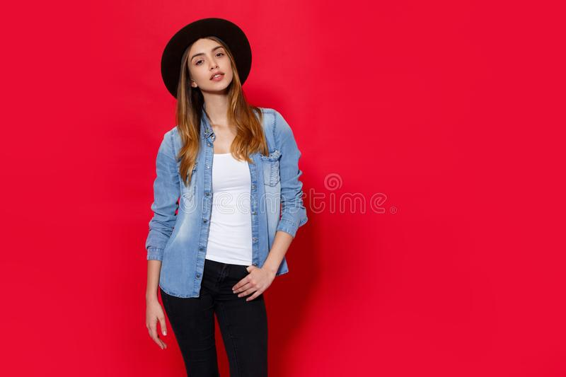 Close up indoor studio fashion portrait of gorgeous woman in stylish hat posing on bright red background. copy space. stock photos