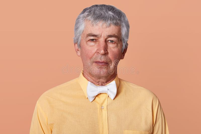 Indoor studio portrait of grey haired serious man looking directly at camera, wearing yellow shirt and white bowtie, having calm stock photos