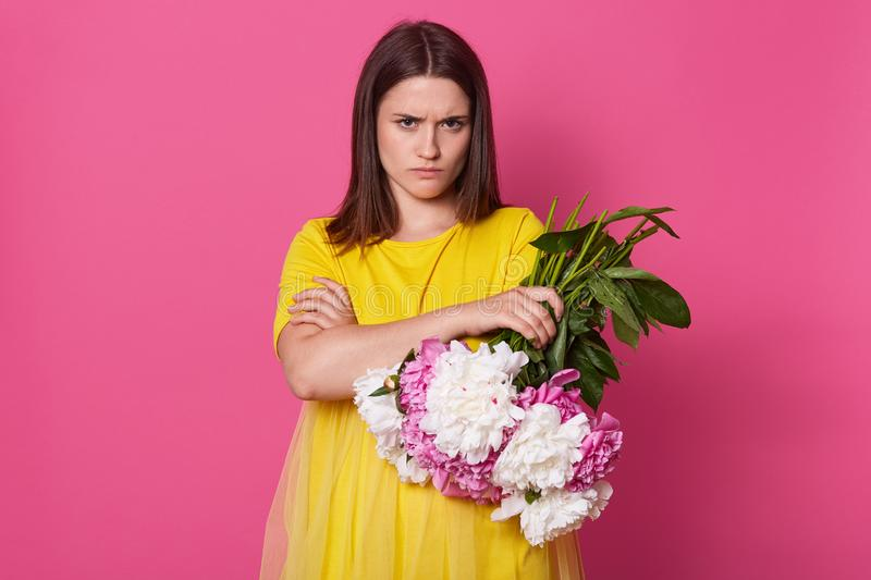 Indoor studio shot of charismatic model with frowned face and folded arms, holding bouquet of white and pink flowers, going to. Throw them out, wearing yellow stock photo