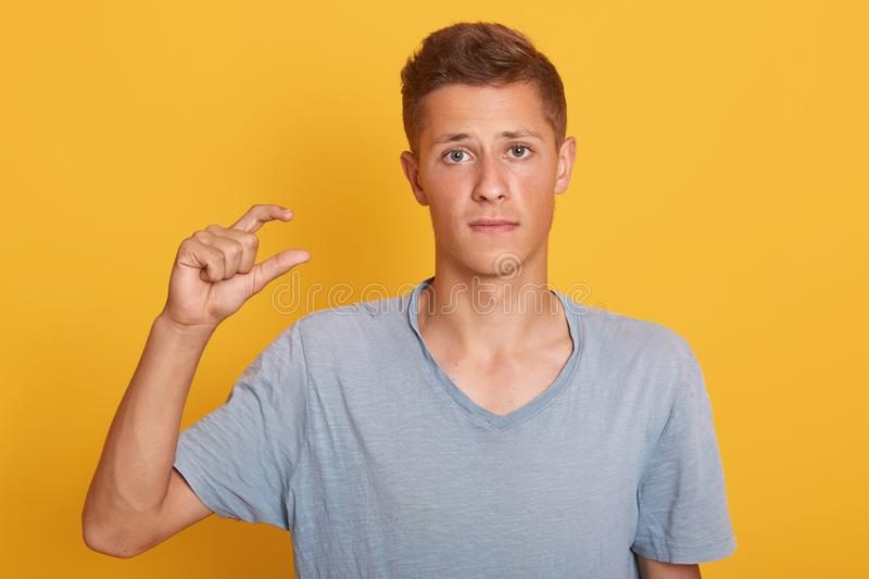 Indoor studio shot of disappointed cute young man looking directly at camera, posing in casual blue t shirt, making gesture, royalty free stock image