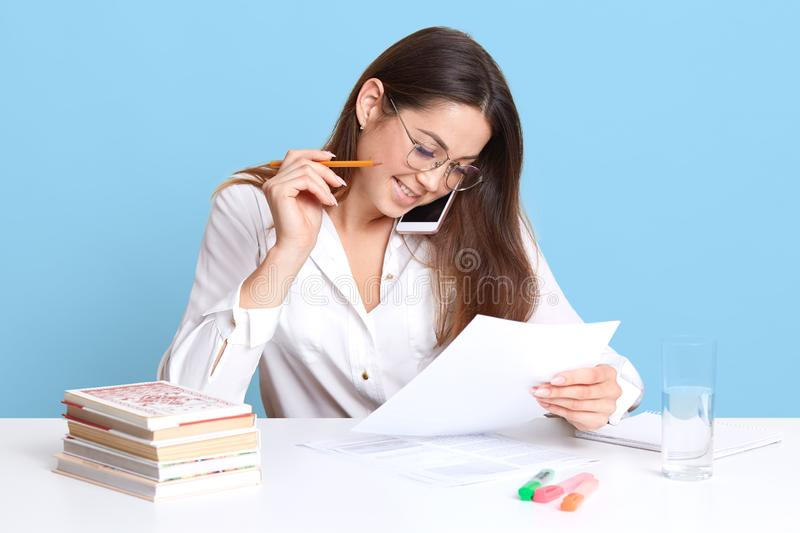 Indoor studio shot of elegant young female sitting at white desk, speaking via smartphone while working at her course work, stock photo