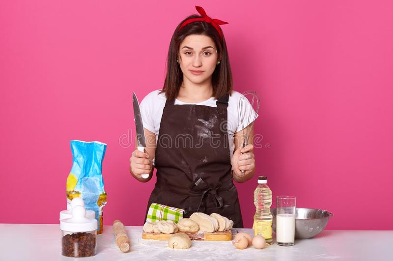 Indoor studio shot of exhausted confident brunette holding whisk and sharp knife in both hands, looking directly at camera,. Standing isolated over pink royalty free stock photos
