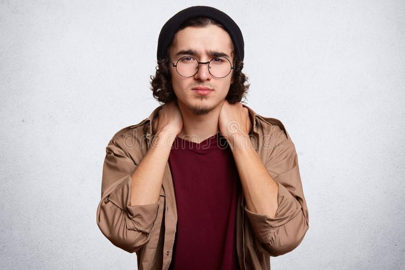Indoor studio shot of handsome serious young guy posing isolated over white background in studio, touching his neck with both royalty free stock photos