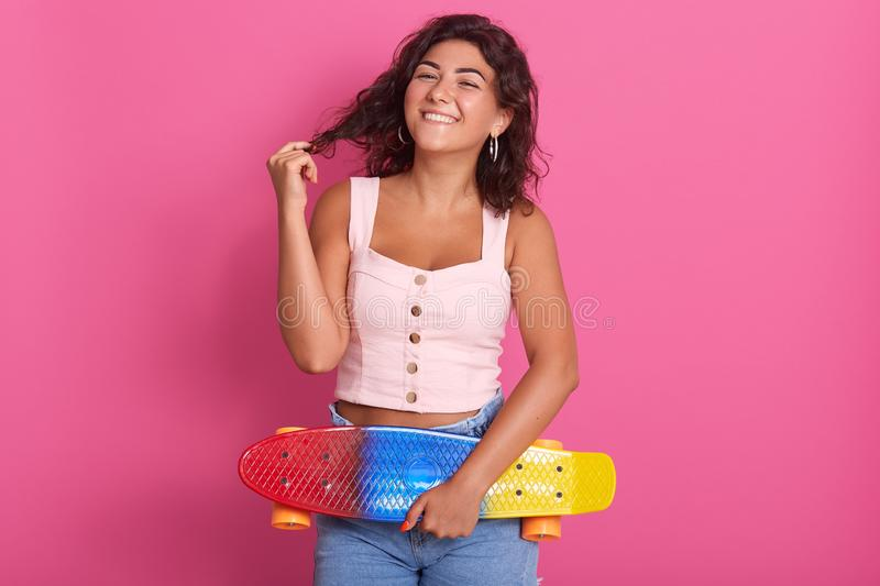 Indoor studio shot of sincere charming model posing over pink background, touching her hair, standing with her skateboard, wearing. Pink top and jeans, looking stock photography