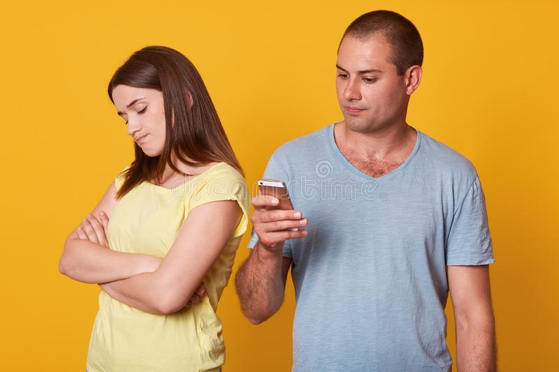 Indoor studio shot of woman being resentful to his boyfriend behavior, looking aside with folded arms, man interested in social. Indoor studio shot of women stock photography