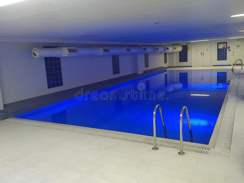 Indoor Swimming Pool. A clean and pristine indoor swimming pool that is underground with illuminate under water lighting stock photo