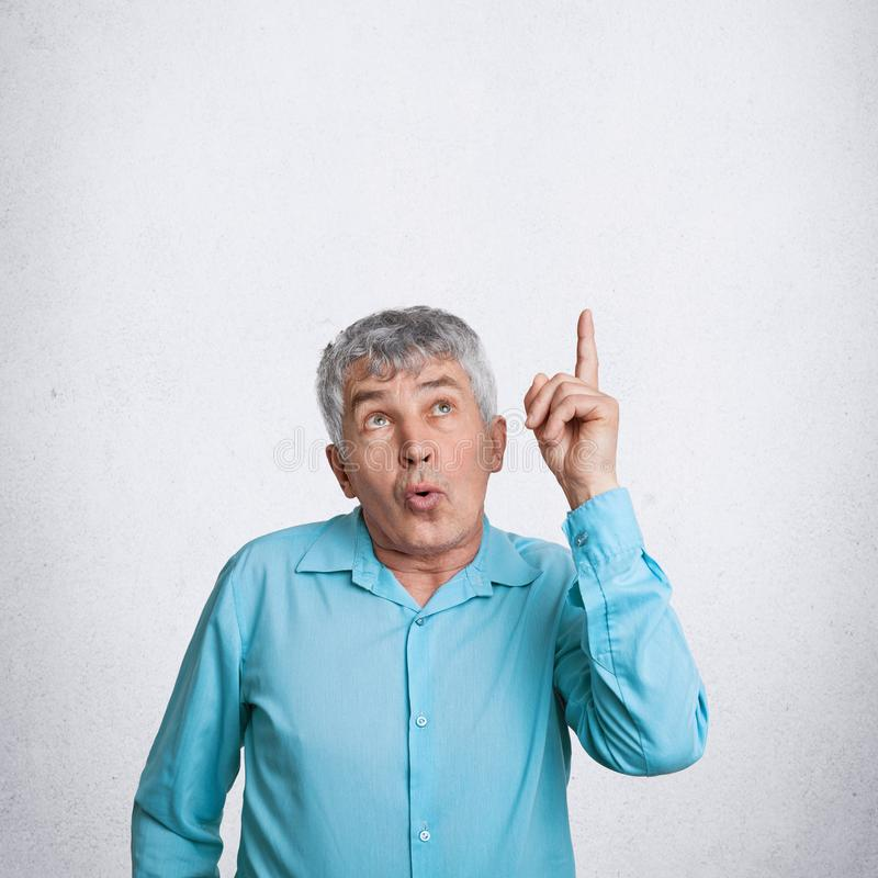 Indoor vertical shot of amazed elderly male indicates upwards as notices something surprising, dressed in elegant shirt, poses aga. Inst white background with stock images