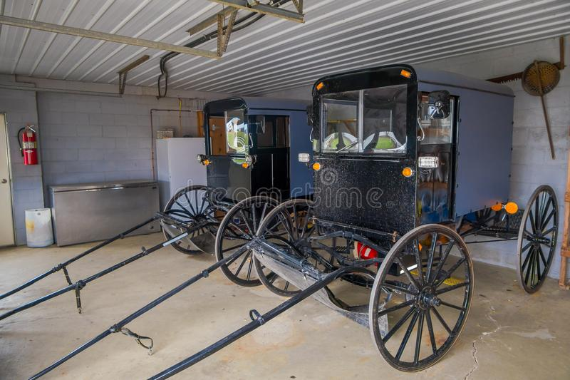 Indoor view of Amish black carriage or buggy parked inside of a garage of a house in Lancaster County royalty free stock photo