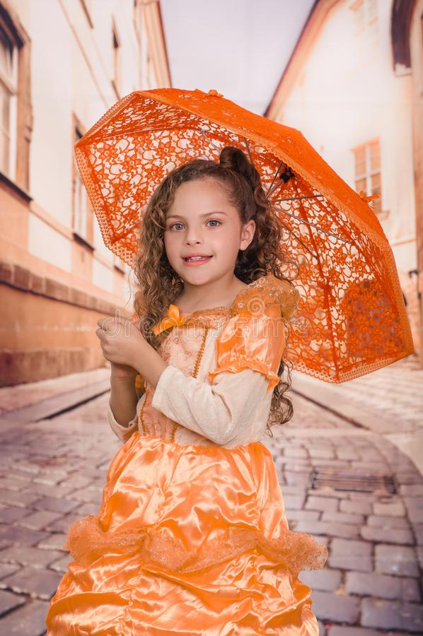 Indoor view of full body of little girl wearing a beautiful colonial costume and holding an orange umbrella in a blurred stock images