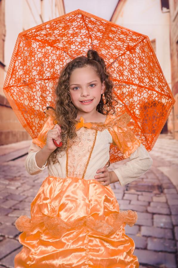 Indoor view of full body of little girl wearing a beautiful colonial costume and holding an orange umbrella in a blurred royalty free stock photos