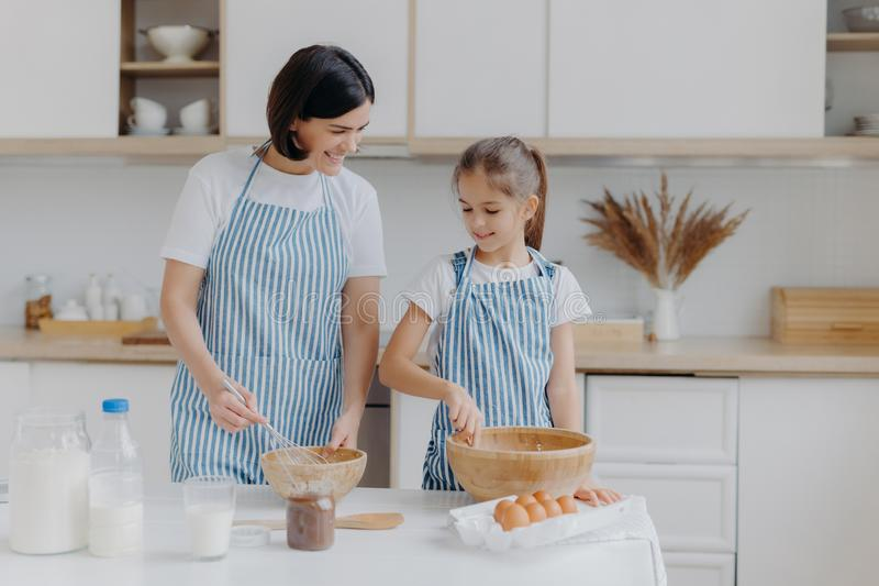 Indoor view of happy mother and daughter prepare tasty supper together, stand next to each other in aprons near kitchen table, stock image