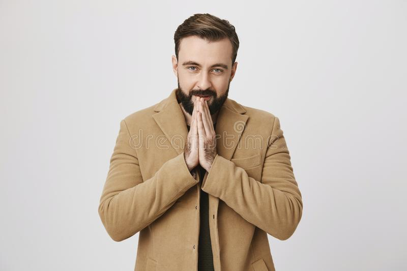 Indoor waist-up portrait of attractive bearded european model in coat, heating hands with warm breath, feeling cold stock image