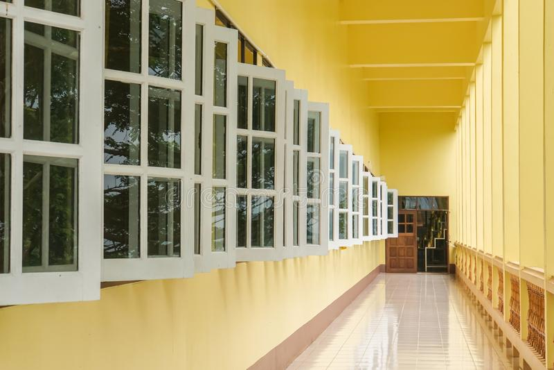 Indoor walkway to the door entrance with vintage windows royalty free stock photo