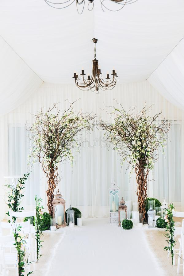Indoor wedding ceremony with white wedding arch decorated with flowers and big white candles.  royalty free stock photography