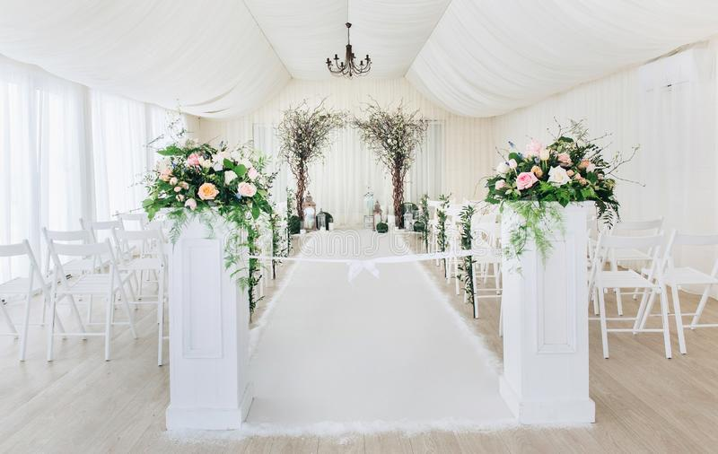Indoor wedding ceremony with white wedding arch decorated with flowers and big white candles.  stock image