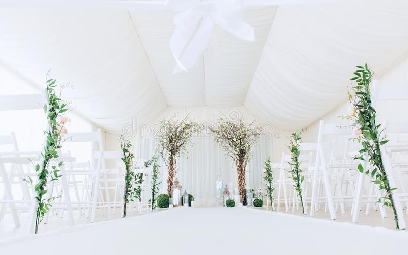 Indoor wedding ceremony with white wedding arch decorated with flowers and big white candles.  royalty free stock image