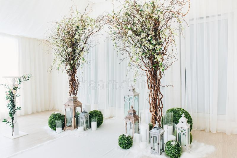 Indoor wedding ceremony with white wedding arch decorated with flowers and big white candles.  stock images