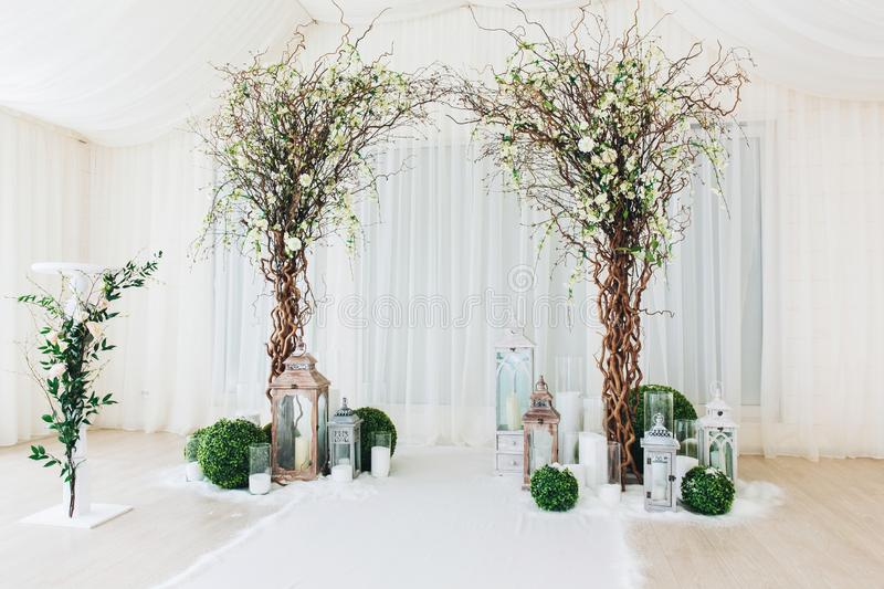 Indoor wedding ceremony with white wedding arch decorated with flowers and big white candles.  royalty free stock photos