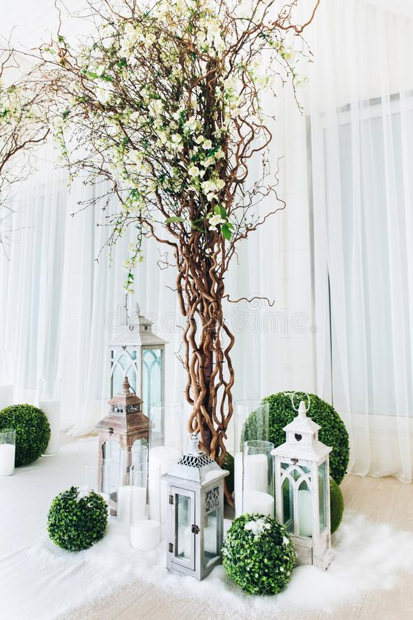 Indoor wedding ceremony with white wedding arch decorated with flowers and big white candles.  stock photos